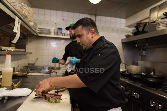 Male chef preparing chicken piece in kitchen at restaurant — Stock Photo