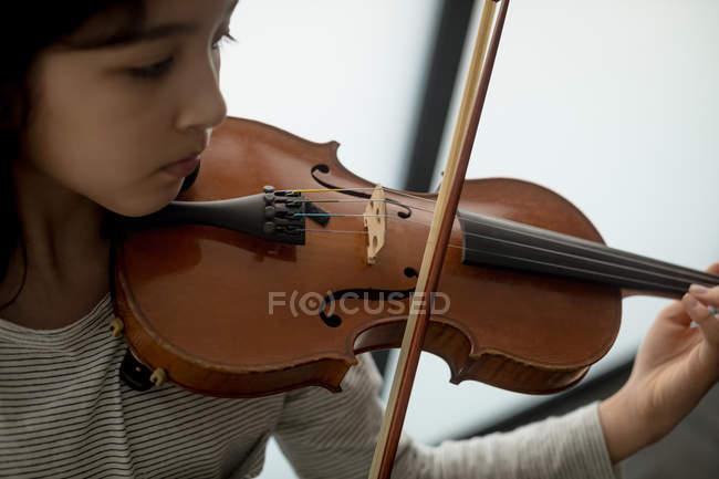 Adorable écolière jouant viloin à l'école de musique — Photo de stock