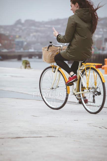 Belle femme utilisant un téléphone mobile tout en faisant du vélo sur la rue — Photo de stock