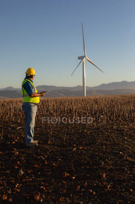 Инженер с помощью мобильного телефона на ветряной электростанции — стоковое фото