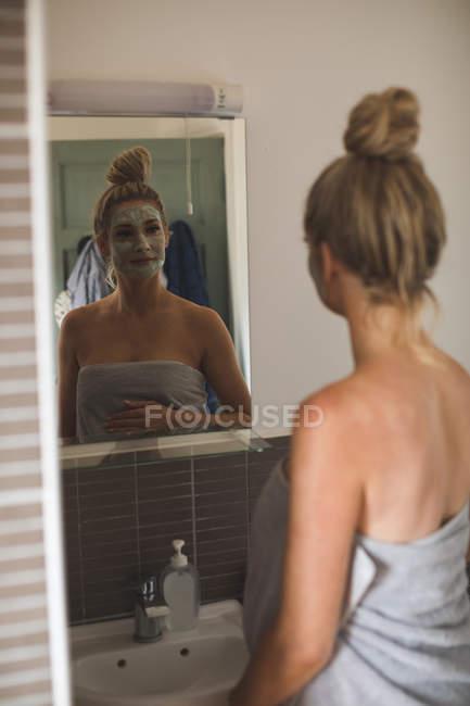 Беременная женщина смотрит на зеркало в ванной комнате дома — стоковое фото