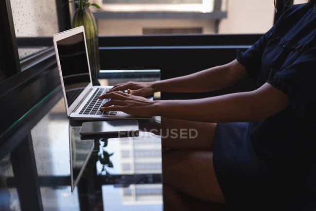 Mittelteil der Geschäftsfrau sitzt und benutzt Laptop im Büro — Stockfoto