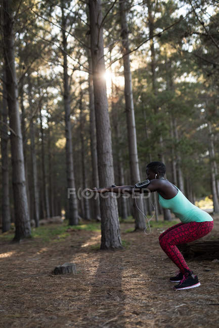 Female athlete performing squats in the forest — Stock Photo