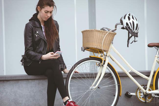 Schöne Frau mit Handy am Bürgersteig — Stockfoto