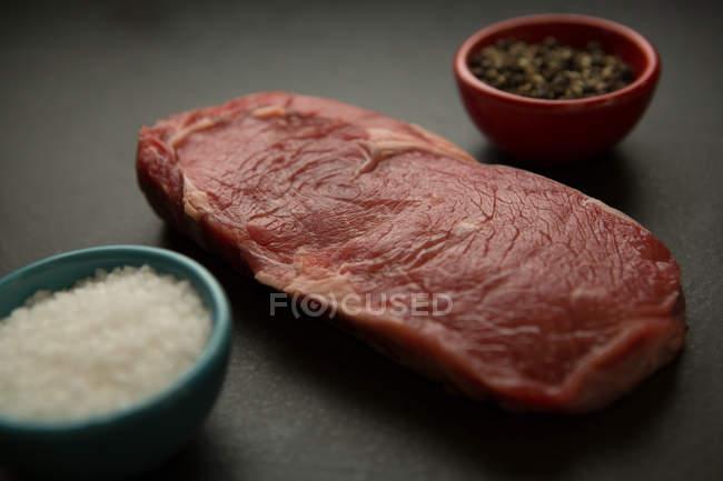 Gros plan sur la viande avec des espèces sur fond de béton — Photo de stock