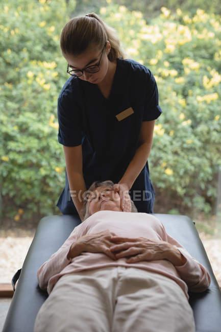 Физиотерапевт, давая голове массаж старший женщине дома — стоковое фото