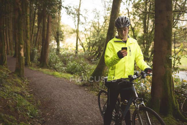 Молодой человек с велосипедом с помощью мобильного телефона в лесу — стоковое фото