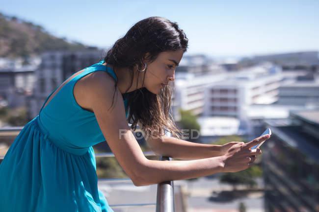 Деловая женщина, опирающаяся на перила во время использования мобильного телефона в солнечный день — стоковое фото