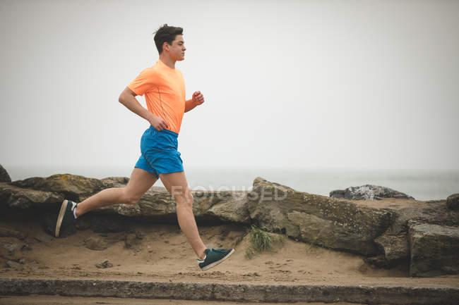 Молодой человек бегает по берегу моря — стоковое фото