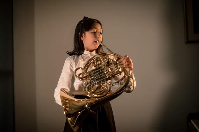 Entzückendes Schulmädchen spielt Waldhorn in der Musikschule — Stockfoto