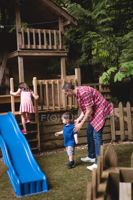 Pai com seu filho e filha no jardim em um dia ensolarado — Fotografia de Stock