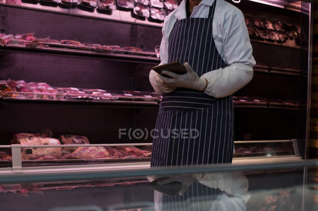 Mid section of butcher using digital tablet in butcher shop — Stock Photo