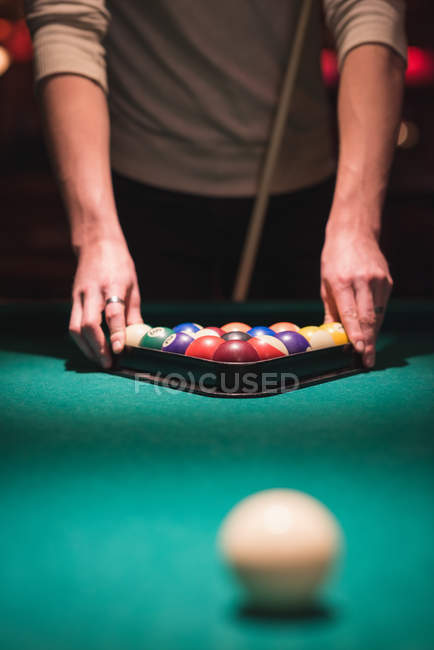 Man arranging snooker balls in triangle rack at night club — Stock Photo