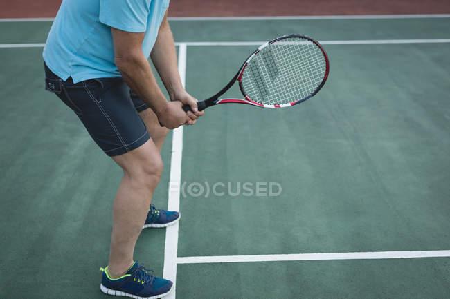 Низький розділ старший людини, що грати в теніс в тенісний корт — стокове фото