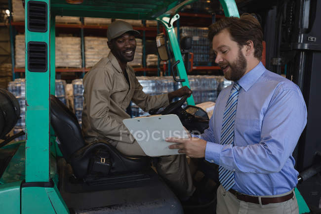 Male workers interacting with each other in warehouse — Stock Photo