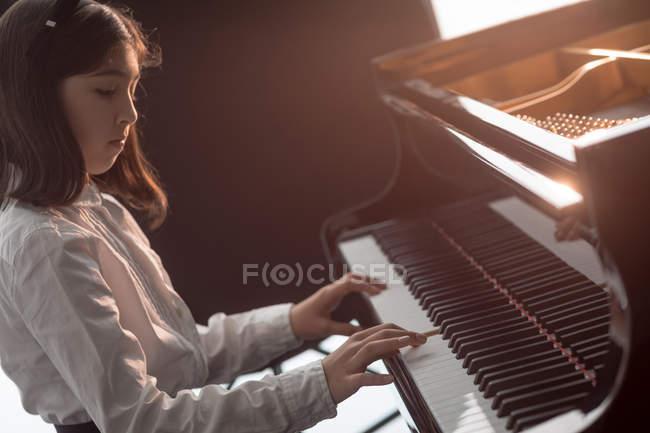 Adorable schoolgirl playing piano in music school — Stock Photo