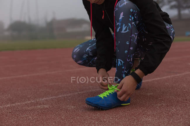 Female athlete tying shoelaces on the running track — Stock Photo