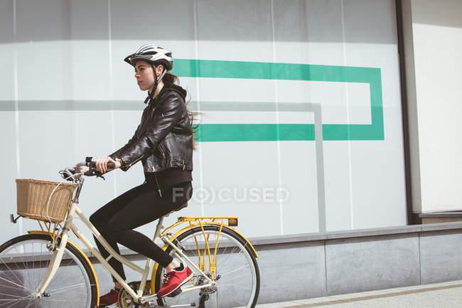 Belle femme en casque vélo d'équitation — Photo de stock