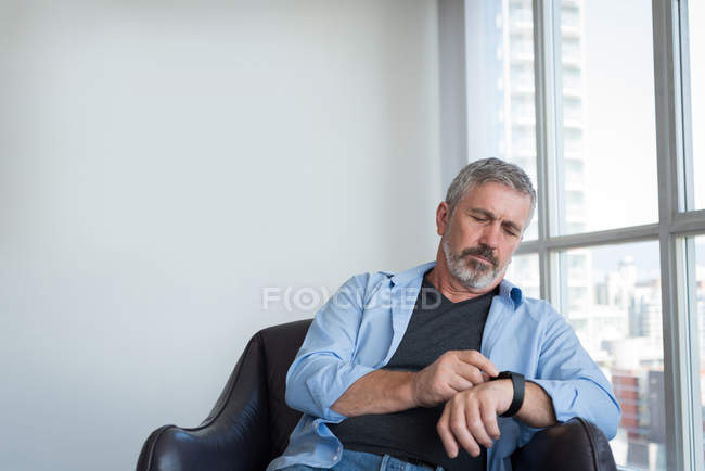 Mature man using smartwatch at home — Stock Photo