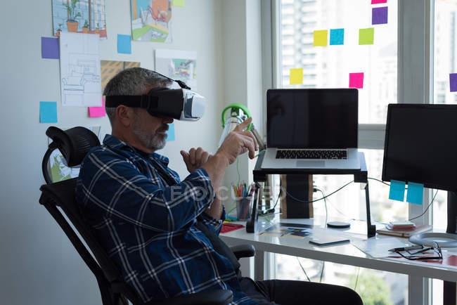 Homme mature utilisant un casque de réalité virtuelle à la maison — Photo de stock