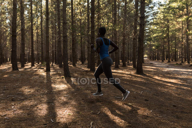 Determined female athlete running in the forest — Stock Photo