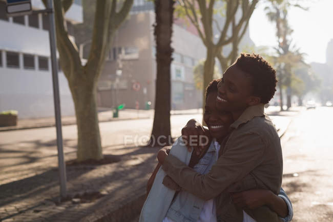 Happy twins siblings embracing each other in city street — Stock Photo