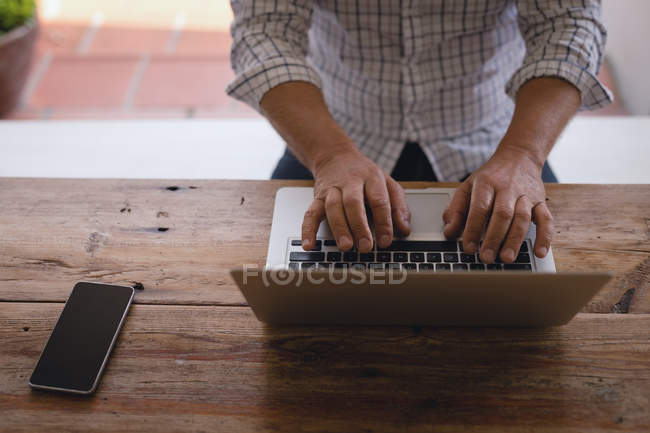 Mid section of man using laptop in porch — Stock Photo