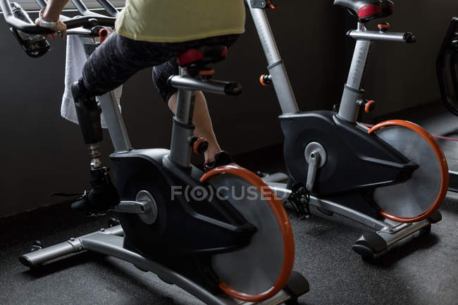 Disabled woman exercising on a gym cycle — Stock Photo