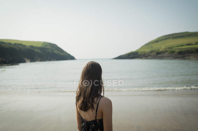 Rear view of woman standing on the beach on a breezy day — Stock Photo
