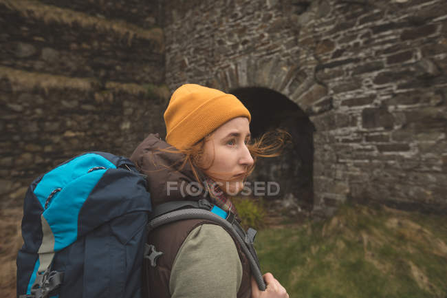 Beautiful female hiker with backpack looking around — Stock Photo