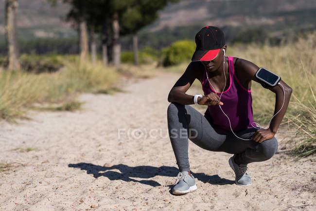 Вымотанная спортсменка приседает в лесу — стоковое фото