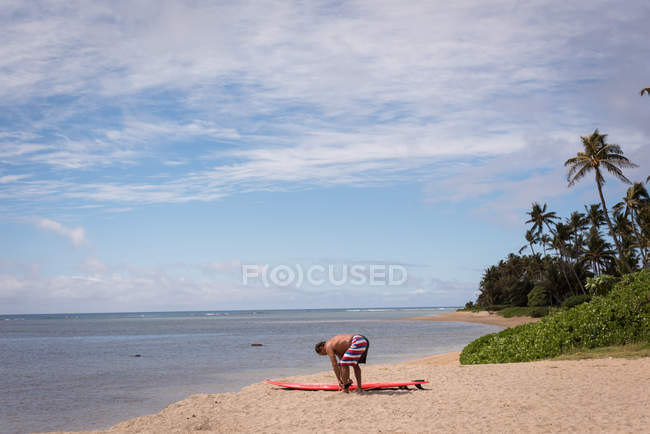 Male surfer holding surfboard at beach — Stock Photo
