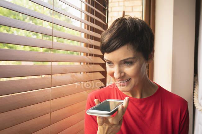 Учасник чемпіонату з мобільного телефону біля вікна будинку — стокове фото