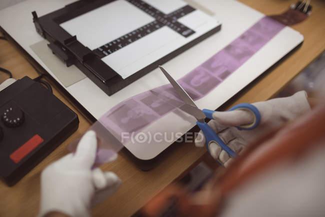 Жіночий фотограф різання кінострічки з фотографіями у фото-студії — стокове фото