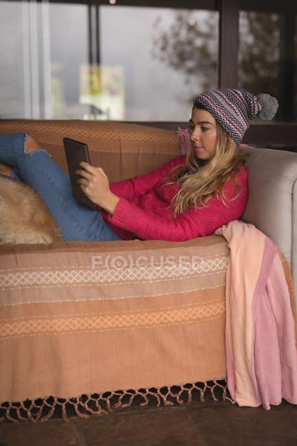 Mädchen mit Hund nutzt digitales Tablet im heimischen Wohnzimmer — Stockfoto