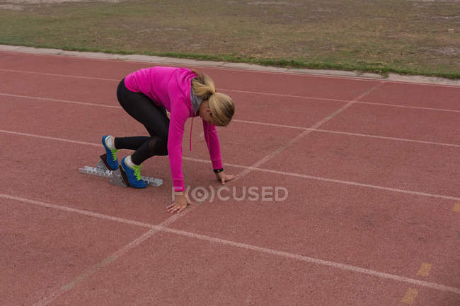 Female athletic ready for the race on the running track — Stock Photo