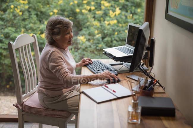 Femme âgée utilisant un ordinateur de bureau à la maison — Photo de stock