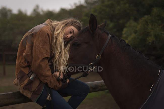 Teenager-Mädchen umarmt Pferd auf der Ranch — Stockfoto