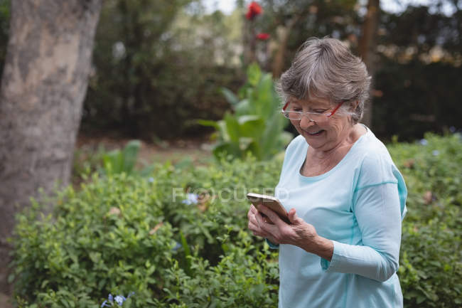 Senior woman using a mobile phone at the backyard — Stock Photo