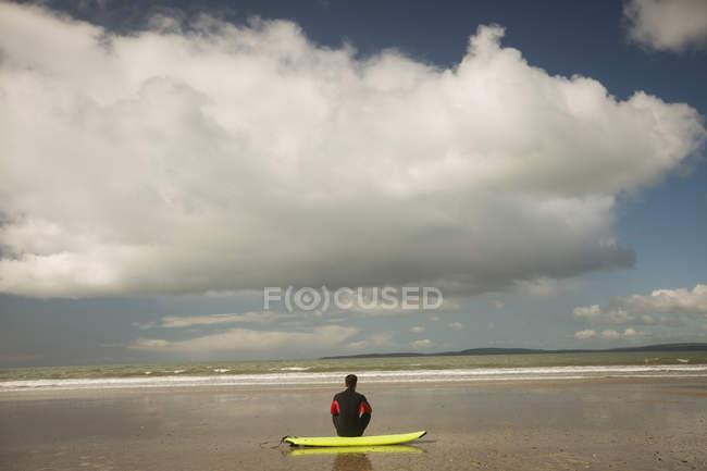 Задній вид серфер, сидячи на дошку для серфінгу на пляжі — стокове фото