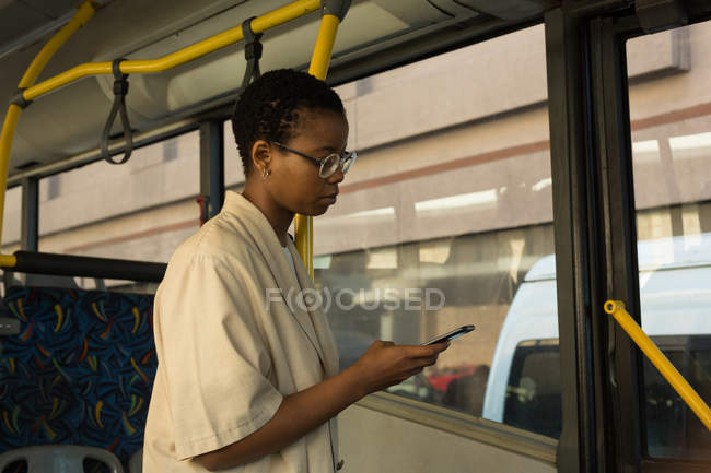 Woman using mobile phone while travelling in the bus — Stock Photo