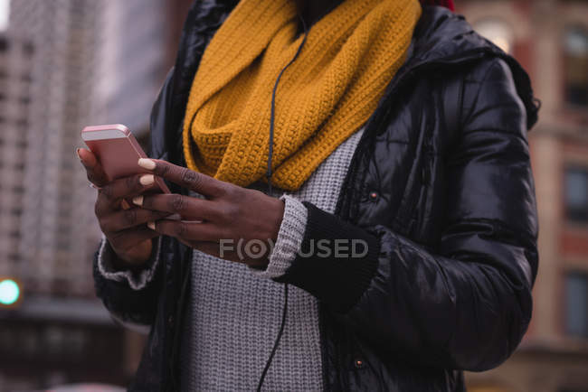 Young woman using mobile phone in city street — Stock Photo