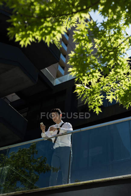 Man having coffee while using mobile phone on a sunny day — Stock Photo
