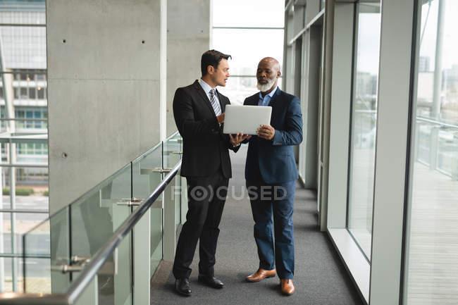 Deux hommes d'affaires discutant sur l'ordinateur portable au bureau — Photo de stock