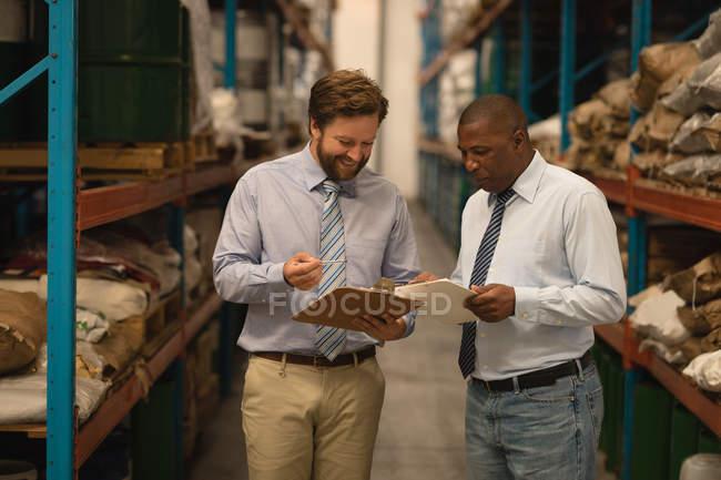 Руководителей-мужчин обсуждать через буфер обмена в складе — стоковое фото