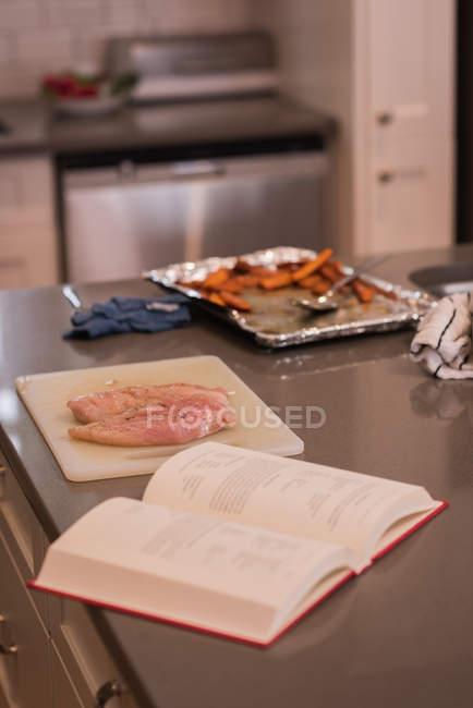 Livre de recette et de la viande dans la cuisine à la maison — Photo de stock
