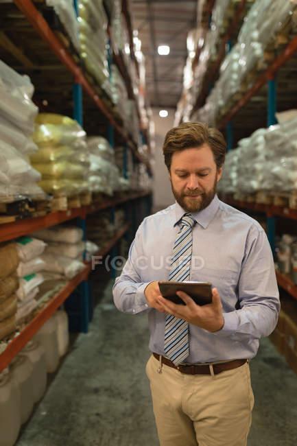 С помощью цифрового планшета на складе мужской менеджер — стоковое фото