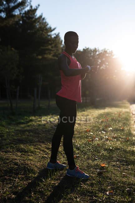 Athlète féminine vérifiant sa smartwatch dans la forêt — Photo de stock