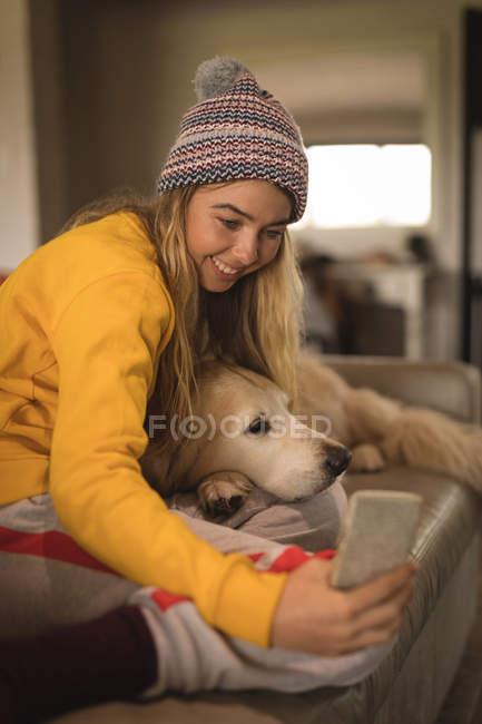 Mädchen macht Selfie mit Hund im heimischen Wohnzimmer — Stockfoto