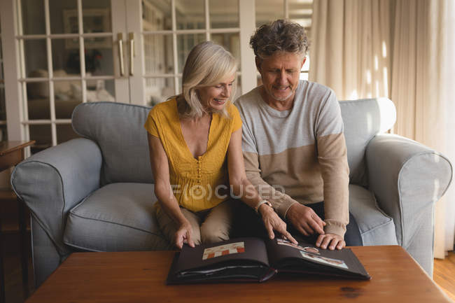 Senior couple looking at photo album at home — Stock Photo